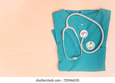 Stethoscope for diagnosis on surgery coat of doctor, on wood table with copy spcae