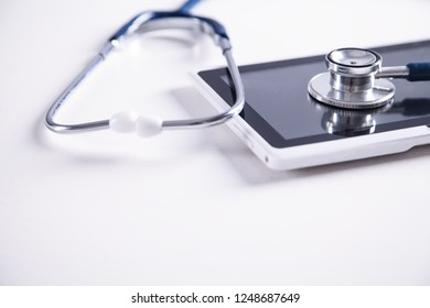 Stethoscope with digital tablet on white desk. Medical equipment. Space for your text