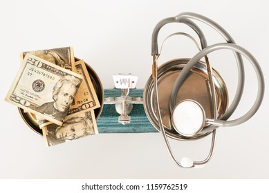 Stethoscope and dollar money in pan weight scale on white background.Health insurance concept.