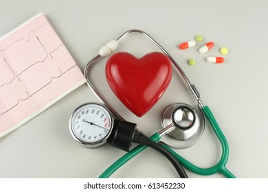 Stethoscope, electrocardiogram, and a red heart on a gray background.