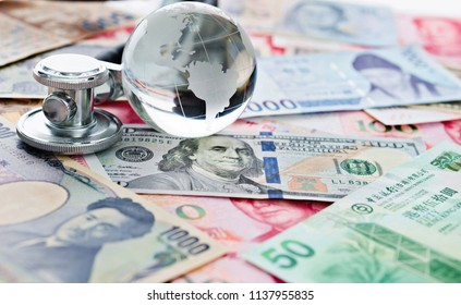 Stethoscope and glass globe on many banknotes, financial health check concept.