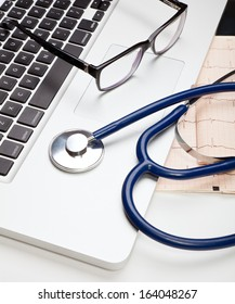 Stethoscope and glasses lying on laptop computer