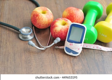 Stethoscope with glucose meter,fruits and dumbbells for using in fitness, concept to control diabetes, Exercise in Diabetes Patients concept.