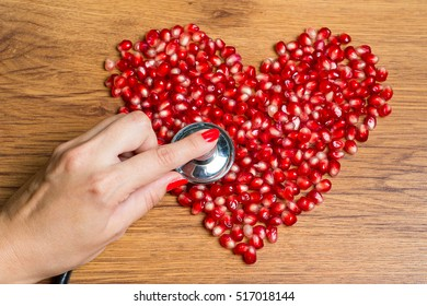 Stethoscope in hand on the heart of the pomegranate seeds. Modern methods of diagnosis and treatment of heart disease. Medical Direction - cardiology.