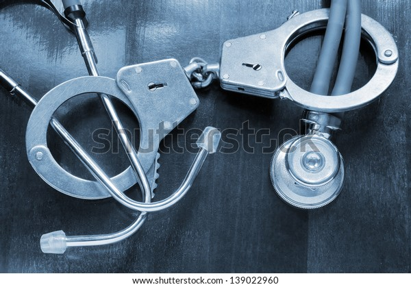 Stethoscope and handcuffs on table