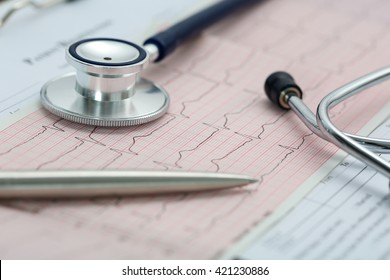 Stethoscope head and silver pen lying on cardiogram on clipboard pad. Cardio therapeutist assistance, physician make cardiac physical, pulse beat measure document, arrhythmia idea, pacemaker concept