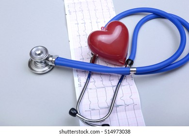 Stethoscope head and silver pen lying on cardiogram on clipboard pad. Cardio therapeutist assistance, physician make cardiac physical, pulse beat measure document, arrhythmia idea, pacemaker concept.