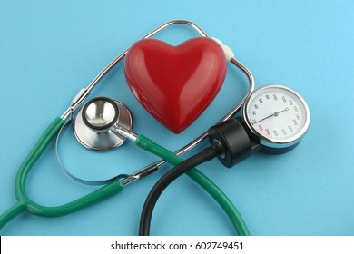 Stethoscope and heart on blue background.