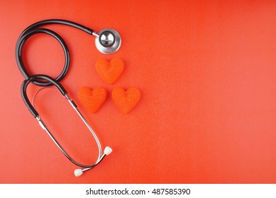 Stethoscope with heart on red background with space for text - health concept. Medical conceptual