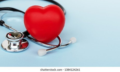 Stethoscope And Heart Shape on Blue Background - Medical and Insurance Concepts