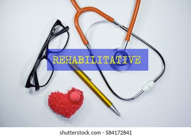 Stethoscope and heart shape on an open book with inscription REHABILITATIVE on a white background. Medical, Healthcare and Wellness concept.