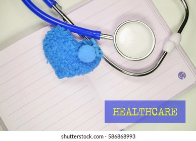 Stethoscope and heart shape on an open book on a white background. Medical, Healthcare and Wellness concept.