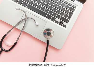 Stethoscope keyboard laptop computer isolated on pink background. Modern medical Information technology and sofware advances concept. Computer and gadget diagnostics and repair. Flat lay top view