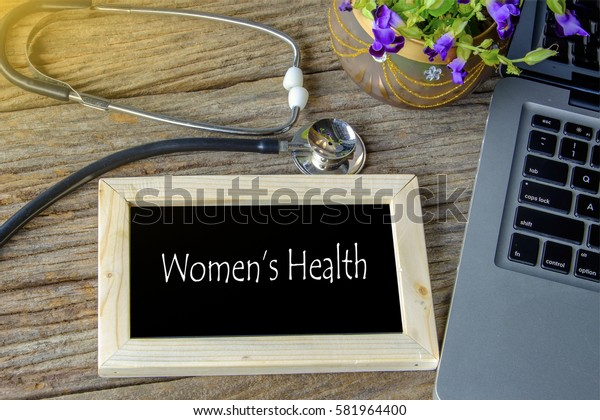 Stethoscope, laptop and flower on wooden table with WOMEN'S HEALTH word as medical concept