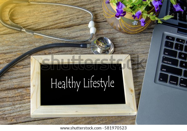 Stethoscope, laptop and flower on wooden table with HEALTHY LIFESTYLE word as medical concept
