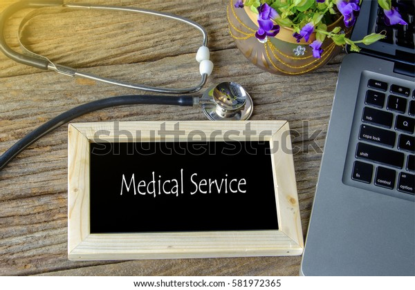 Stethoscope, laptop and flower on wooden table with MEDICAL SERVICE  word as medical concept
