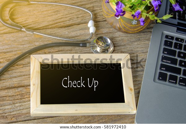 Stethoscope, laptop and flower on wooden table with CHECK UP word as medical concept