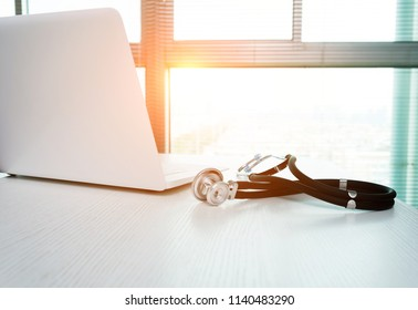 Stethoscope and laptop on doctor working desk.