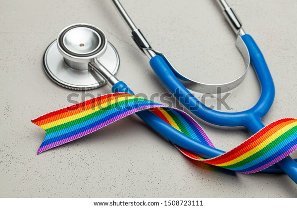 Stethoscope and LGBT rainbow ribbon pride symbol. Medical support after sex reassignment surgery. Grey background.