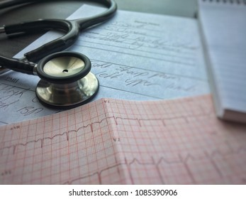 A stethoscope lying on mock-up doctor's notes and an electrocardiogram (ECG) read out. Doctor's handwriting. Health care professional's tool for examining patients.