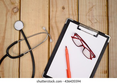Stethoscope with medical clip board on wooden background. ( Medical Concept )