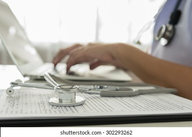 Stethoscope, medical document with the doctor using computer in room at hospital.