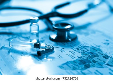 Stethoscope medical drug vaccine syringe needle hypodermic injection treatment on map world ,Medical concept tourism travel care diseases Healthy .blue background. selective focus stethoscope map