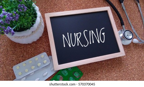Stethoscope, Medicine, Chalk board and flower with inscription NURSING on a wooden table. Medical and health care concept.