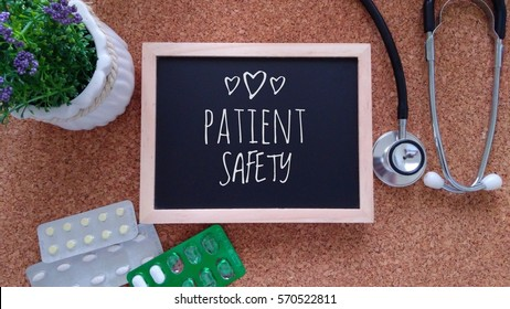 Stethoscope, Medicine, Chalk board and flower with inscription patient safety on a wooden table. Medical and health care concept.
