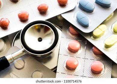 Stethoscope, medicine and pills close up