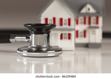 Stethoscope and Model House on Gradated Background with Selective Focus.