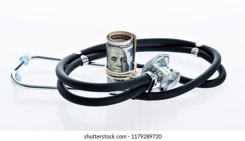 Stethoscope and money dollar cash isolated on white background.