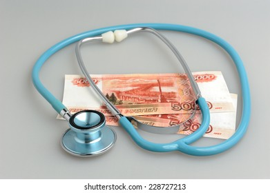 Stethoscope and money on gray background