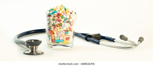 stethoscope with multiple pills and dtug filled in the glass