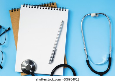 Stethoscope, notebook, glasses and pen on a blue table, concept of health and medicine