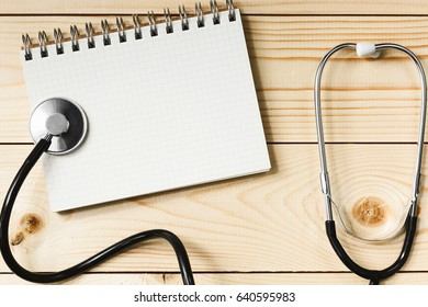Stethoscope and notebook on a light wooden table, the concept of health and medicine