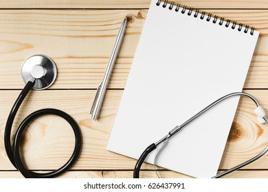 Stethoscope, notebook and pen on a light wooden table, concept of health and medicine
