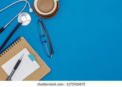 Stethoscope with notebook ,pen, white paper ,coffee cup,glasses, on blue background,Medical background concept.