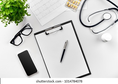 Stethoscope in the office of doctors.Top view of doctor's desk table, blank paper on clipboard with pen. Copy space. Designer's blank