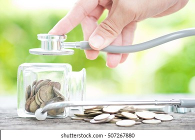 Stethoscope on bottle and coin on wooden background. Concept for finance health check or cost of business, financial analysis, audit or accounting.