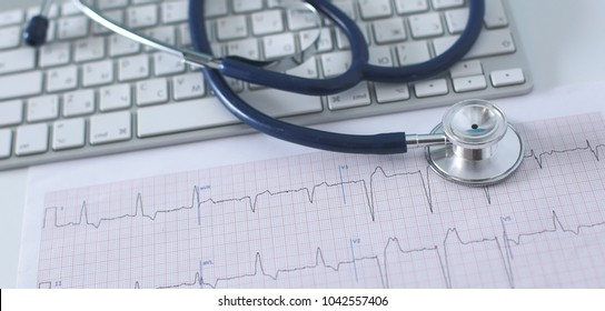 Stethoscope on cardiogram concept for heart care on the desk.blue toned images