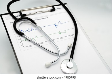 Stethoscope on clipboard over blood pressure graph printout