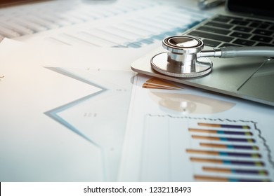 Stethoscope on computer with test results in Doctor consulting room background and report chart for medical costs in modern hospital on Laptop desk. Healthcare costs business and fees concept.
