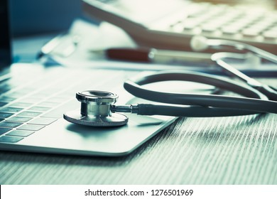 Stethoscope on computer with test results in Doctor consulting room background and report chart for medical costs in modern hospital on Laptop desk. Healthcare costs business, fees concept. Gray tone