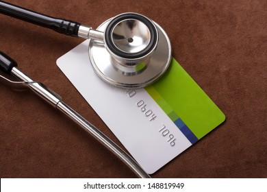 Stethoscope on a credit card concept with a brown background