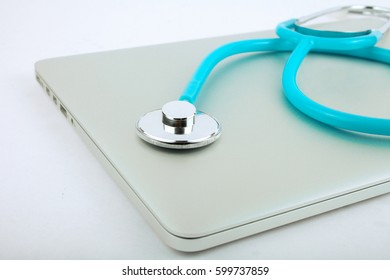 Stethoscope on a laptop, isolated on white background with a selective focus