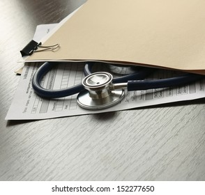 Stethoscope on medical billing statement on table