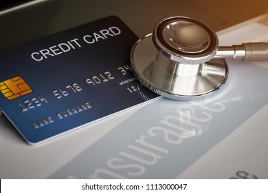Stethoscope on Mock up Credit Card with number on cardholder in hospital desk. Health insurance and cost of care, self-care during illness using payments card for medicals service.
