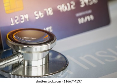Stethoscope on Mock up Credit Card with number on cardholder in hospital desk. Health insurance and cost of care, self-care during illness using payments card for medicals service. Soft focus
