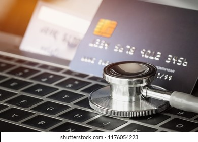 Stethoscope on Mock up Credit Card with number on card at computer in hostpital desk. Health insurance and cost of medical care, self-care during illness using using payments card for medicals service